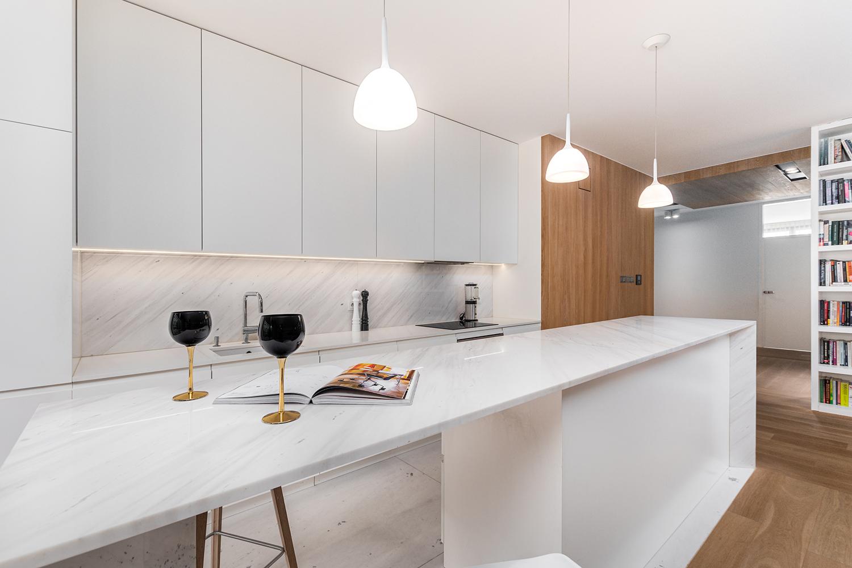Zdjęcie wnętrza - marmurowy blat kuchenny z kieliszkami na tle aneksu kuchennego