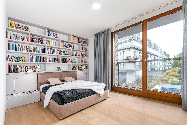 Zdjęcie wnętrza - dwuosobowe łóżko z półkami pełnymi książek i okno z widokiem na blok