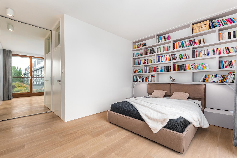 Zdjęcie wnętrza - dwuosobowe łóżko z półkami pełnymi książek i lustro w sypialni