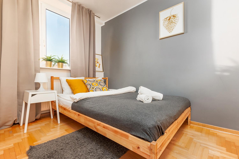 Zdjęcie wnętrza - łóżko dwuosobowe z szafką nocną przy oknie w sypialni