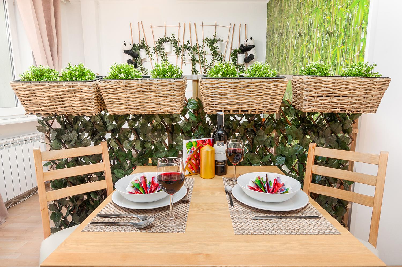 Zdjęcie wnętrza - 4 wiklinowe koszyki z kwiatami nad zastawionym stołem