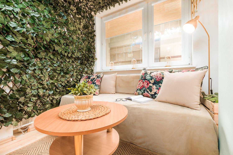 Zdjęcie wnętrza - sofa i stolik kawowy przy oknie w altanie pełnej bluszczu