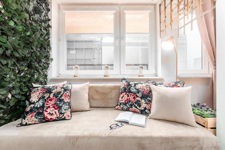 Zdjęcie wnętrza - poduszki, okulary i otwarta książka na sofie przy oknie