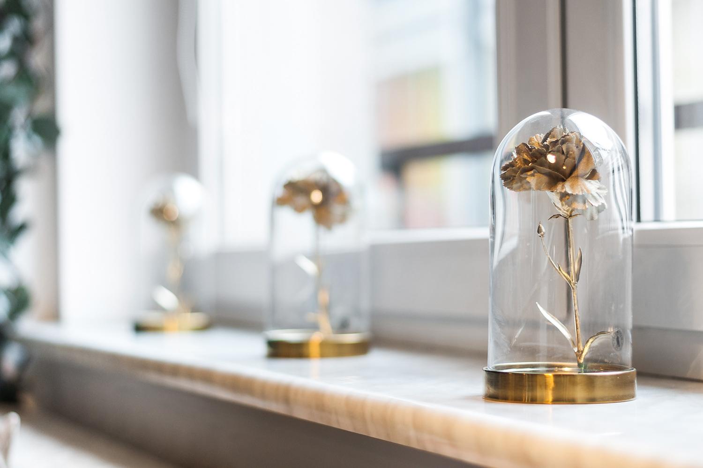 Zdjęcie wnętrza - złota róża w szklanej kopule na parapecie