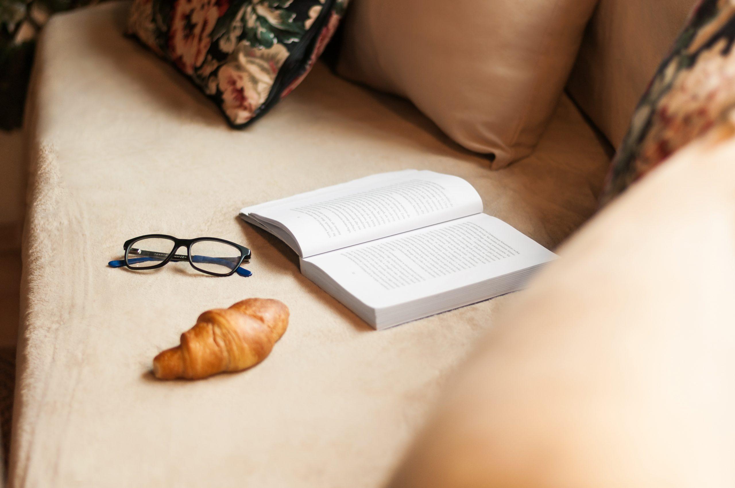 Zdjęcie wnętrza - otwarta książka, okulara i coissant na beżowej sofie