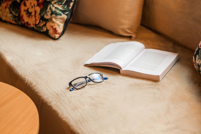 Zdjęcie wnętrza - otwarta książka i okulara na beżowej sofie
